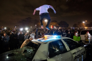 An anti-Trump protester jumps on top of a police vehicle caving in the roof as protesters fill the streets in front of the Orange County Fair & Event Center along Fair Drive after the Trump rally let out in Costa Mesa, California on Thursday, April 28, 2016. (Jose Lopez)